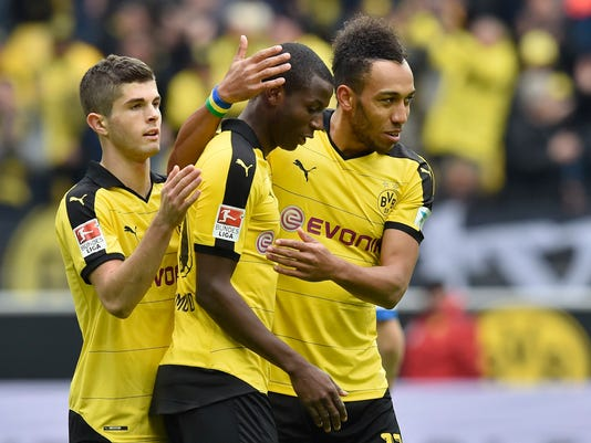 Dortmund's Adrian Ramos is celebrated by teammates Pierre-Emerick Aubameyang, right, and Christian Pulisic, left, after scoring his second goal during the German Bundesliga soccer match between Borussia Dortmund and Hamburger SV in Dortmund, Germany, Sunday, April 17, 2016. (AP Photo/Martin Meissner)