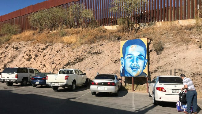 In this Dec. 4, 2017, file photo, a portrait of 16-year-old Mexican youth Jose Antonio Elena Rodriguez, who was shot and killed in Nogales, Sonora, Mexico, is displayed on the Nogales street where he was killed that runs parallel with the U.S. border. A U.S. Border Patrol agent who was acquitted of second-degree murder in a case that ended in mistrial will be retried on lesser charges, the attorney for the family of the rock-throwing teen killed in a 2012 cross-border shooting said Friday, May 11, 2018.