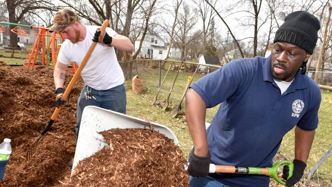 Pontiac DPW employees Andrew Langlois, left, and Victor Stevens, both of Pontiac, volunteers as they fill up wheel barrows with multch at Madge Burt Park.