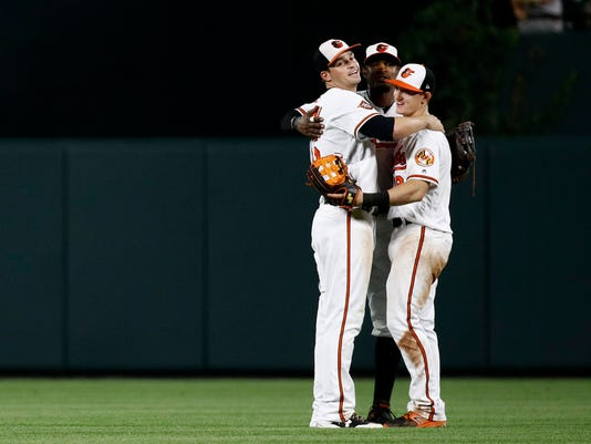 Baltimore Orioles outfielders Trey Mancini, from left, Adam Jones and Austin Hays embrace after a baseball game against the Tampa Bay Rays in Baltimore, Thursday, Sept. 21, 2017. Baltimore won 3-1. (AP Photo/Patrick Semansky)