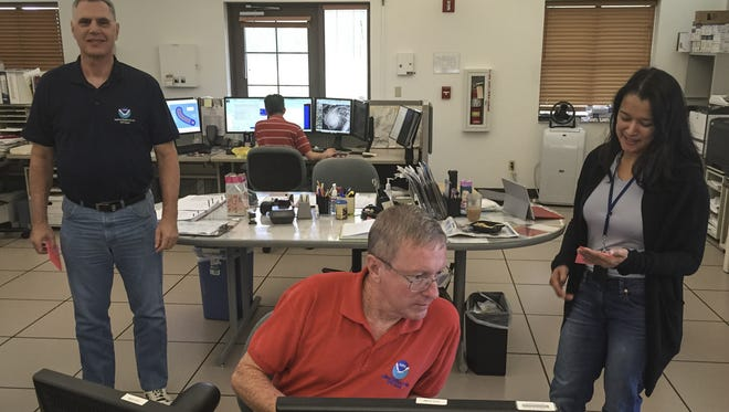 From right, meteorologist in charge Jenny Miller, forecaster Mike Middlebrooke, and meteorologist Rich Devita track the approaching Typhoon Dolphin from the National Weather Service operations room in Tiyan on May 15.