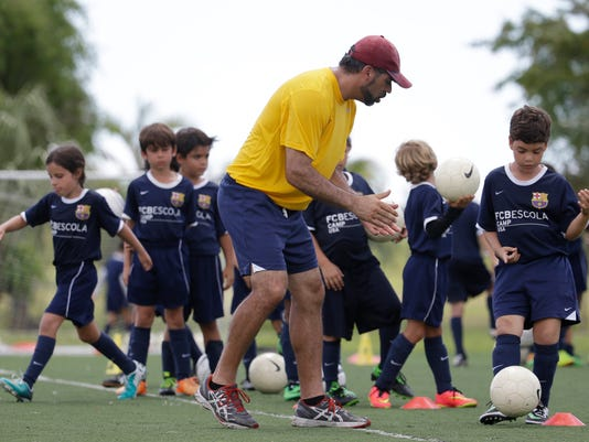 In this Thursday, Aug. 1, 2014 photo, Lee Santamaria, front, of Cooper City, Fla., works with children during a soccer camp held by FC Barcelona in Miami. European clubs like Barcelona, Liverpool and Arsenal have long sent coaches to work at U.S. summer camps, but now some are opening year-round U.S. academies aimed at finding new talent but also to expand their fan bases. This is part of a number of initiatives of major teams to grow their brands in the U.S. (AP Photo/Lynne Sladky)