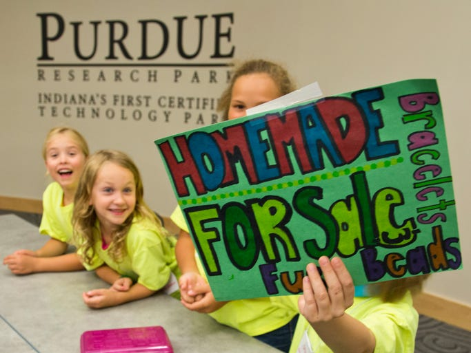 Kaydence Larrison holds a sign trying to lure customers to her group's table during the â??Just Us Entrepreneursâ? program Monday, August 4, 2014, at the at the Kurz Purdue Technology Center in West Lafayette. The children from Just Us Kids childcare center learned about business through the program.