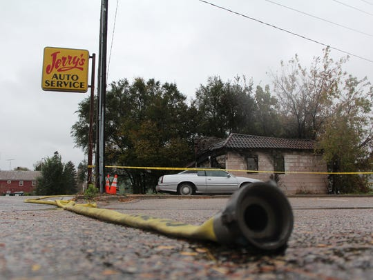 A hose lays on the ground near Jerry's Auto Service