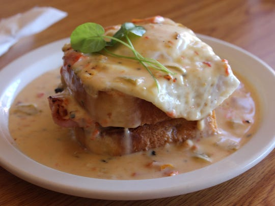 The Madame Mesilla, thick-cut honey ham and cheese between two toasted slices of fresh baked bread with a fried egg and smothered in creamy green sauce, served during brunch hours at Chala's Wood Fire Grill, 2790 Avenida de Mesilla.