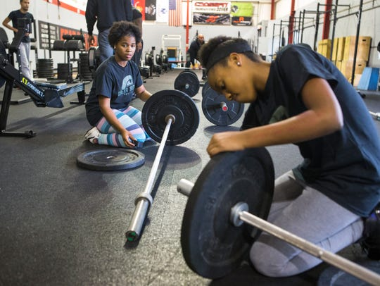 Brieonna Brown, left, and Jalaya Williams rack weights onto a weight bar during a Green Beret Project class at Crossfit Dover where they learn to train others after spending time in the program.