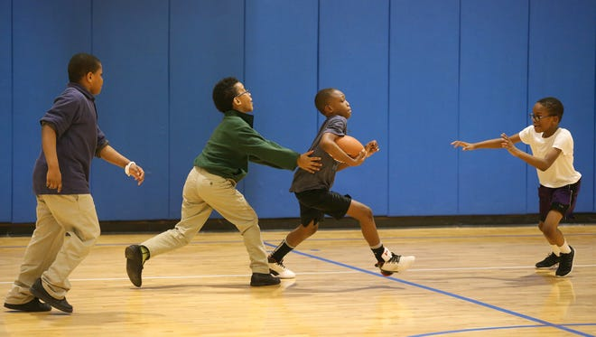 Anttwan Brown, center, plays football in the gym with friends at the Boys & Girls Club of Rochester. The club is open to all children ages 6 to 18, but most live nearby, in a ZIP code where the average annual household income is $24,000.