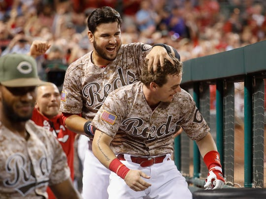 Cincinnati Reds' Scooter Gennett, center right, celebrates with Eugenio Suarez, center left, after Gennett hit his fourth home run in Tuesday's game against the Cardinals.