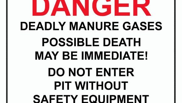 Signs warn farm workers about the potential presence of deadly manure gases.