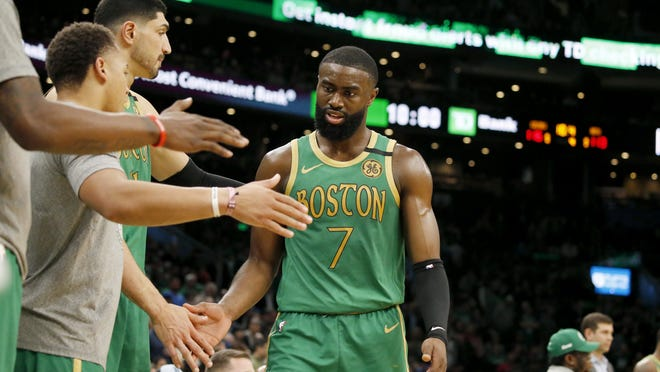 Boston Celtics guard Jaylen Brown (7) is congratulated by teammates at the bench as he takes a break during a game against the Brooklyn Nets, Tuesday, March 3, in Boston.