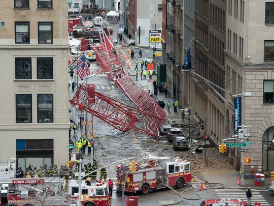 A collapsed crane fills the street on Friday, Feb. 5, 2016, in New York. The huge construction crane was being lowered to safety in a snow squall when plummeted onto the street in the Tribeca neighborhood of lower Manhattan.