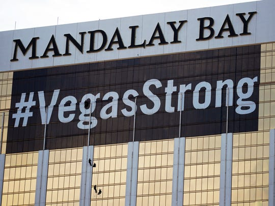 """FILE - In this Monday, Oct. 16, 2017, file photo, workers install a #VegasStrong banner on the Mandalay Bay hotel and casino in Las Vegas. Stephen Paddock opened fire from the hotel on an outdoor country music concert, killing 58 and injuring hundreds. Las Vegas' efforts to rebrand itself since the shooting show just how difficult it can be for organizations to hit the right tone after a deeply tragic event. The city put its famous """"What happens here, stays here"""" slogan on hold, and its initial ad campaign after the attack won praise for its sensitivity. But a national TV commercial that features real social media posts from after the shooting is getting more mixed reviews, with some calling it tacky.(AP Photo/John Locher, File)"""