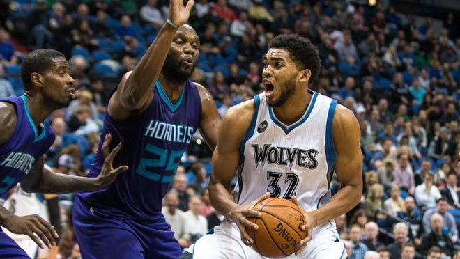 Minnesota Timberwolves center Karl-Anthony Towns (32) dribbles around Charlotte Hornets center Al Jefferson (25) during the third quarter Tuesday at Target Center in Minneapolis. The Hornets defeated the Timberwolves 104-95.