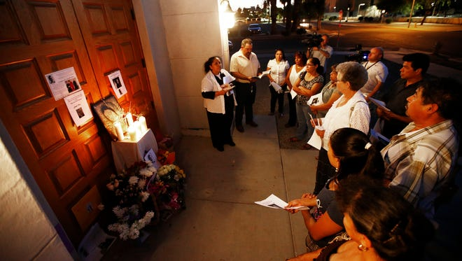 Sarah and Juan Gutierrez (back center) lead a candlelight vigil in honor of Father Kenneth Walker Thursday evening, June 12, 2014 at the site of the shooting at Mater Misericordiae (Mother of Mercy) Mission in Phoenix, AZ. Father Kenneth Walker, 28, was shot and killed and Father Joseph Terra was wounded at the Catholic church Wednesday night near the state Capitol.