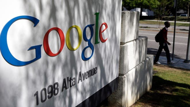 A man walks past a Google sign at the company's headquarters in Mountain View, Calif., this month.