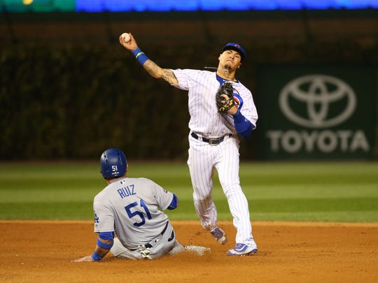 Chicago second baseman Javier Baez turns a double play