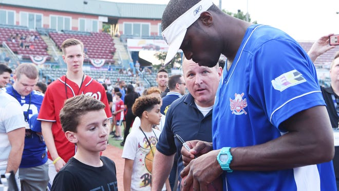 Former NFL player Plaxico Burress signs a football for Ryan Libolt, 13, of the Town of Poughkeepsie, before a charity softball game at Dutchess Stadium.