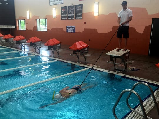 Ashley Davis swims in the pol at the Washington City Community Center while swim coach Jordan Fletcher holds on to an elastic cord tied to her waist and evaluates her stroke during the Balanced Art Multisport triathlon camp Friday, April 14, 2016.
