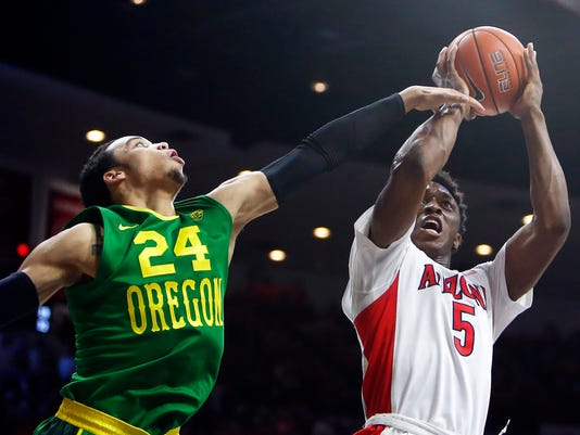 Arizona forward Stanley Johnson (5) shoots next to Oregon forward Dillon Brooks during the second half of an NCAA college basketball game, Wednesday, Jan. 28, 2015, in Tucson, Ariz. (AP Photo/Rick Scuteri)