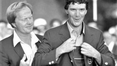 Jack Nicklaus looks on as Augusta native and Masters champ Larry Mize tries on his jacket after 1987 victory.