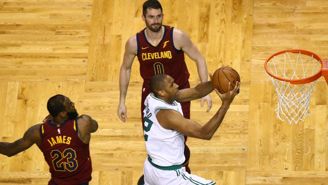 The Celtics' Al Horford drives to the basket against LeBron James, left, and Kevin Love #0 of the Cleveland Cavaliers during during the Celtics' win over the Cavs Sunday in Game 1 of the Eastern Conference finals.