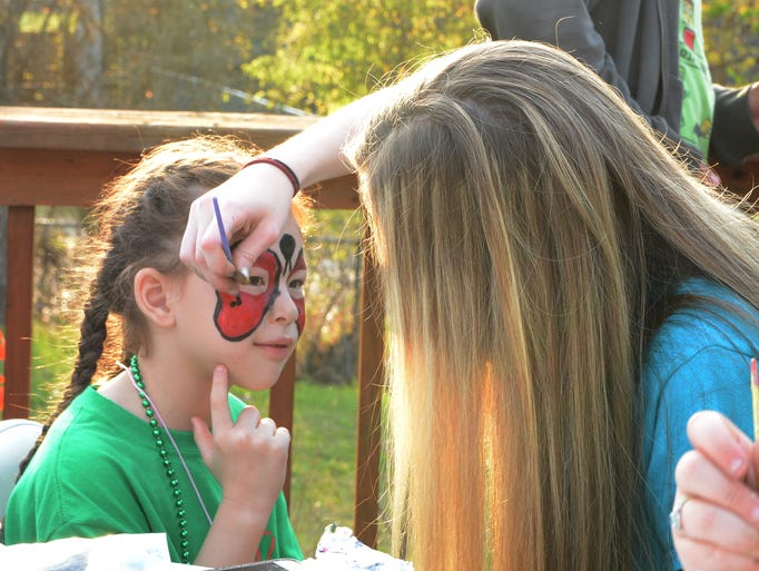 A girl gets her face painted during the Irish-Italian