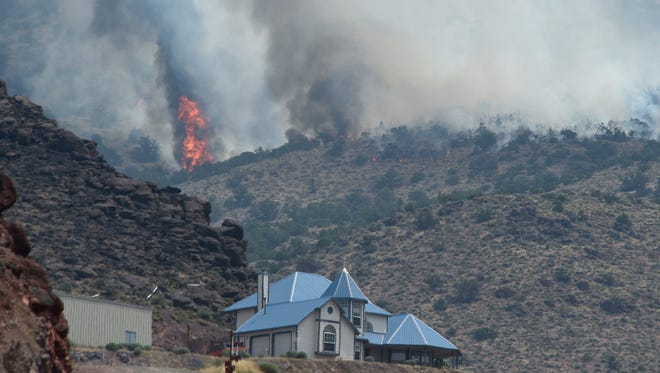 The Perry Fire is seen burning just above a home at 300 Chieftain Dr. in Palomino Valley, north of Reno, on July 31, 2018.