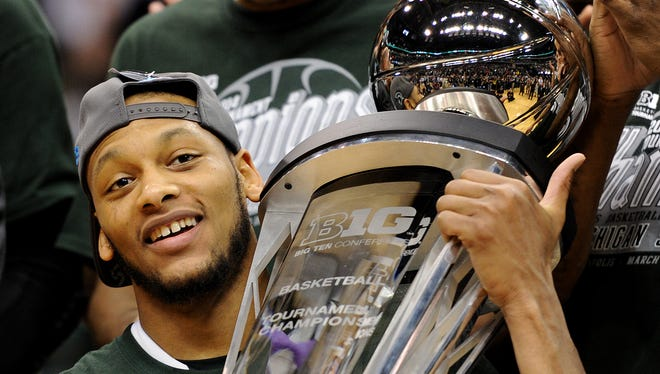 Michigan State forward Adreian Payne holds the championship trophy after beating Michigan to win the championship game of the Big Ten Basketball Tournament inside Bankers Life Fieldhouse, Sunday, March 16, 2014, in Indianapolis. Michigan State won the game 69-55.