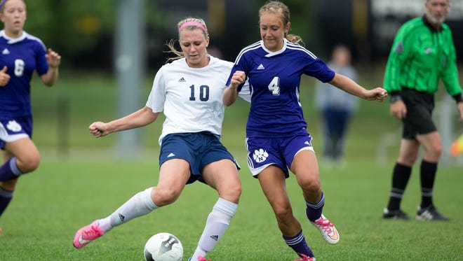 Regina High School's Kennedy Brown kicks the ball around Neveda's Michaela Matuska in the second half Friday, June 12, 2015, during the IHSAA State Soccer Championships at the Cownie Soccer Complex in Des Moines.
