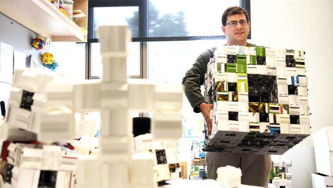 Willamette University assistant math professor Josh Laison and many staff and students are taking part in the global MegaMenger project, folding thousands of business cards into cubes and fractals.