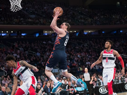 New York Knicks forward Mario Hezonja (8) goes to the basket between Washington Wizards forward Devin Robinson (7) and forward Troy Brown Jr. (6) during the second half of an NBA basketball game Sunday, April 7, 2019, at Madison Square Garden in New York. The Knicks won 113-110. (AP Photo/Mary Altaffer)