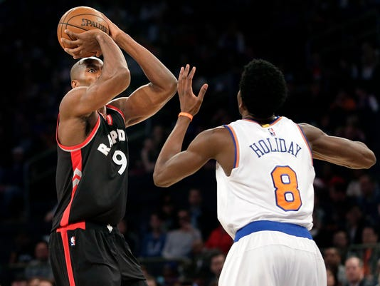 Toronto Raptors' Serge Ibaka, left, takes a shot over New York Knicks' Justin Holiday during the first half of an NBA basketball game, Sunday, April 9, 2017, in New York. (AP Photo/Seth Wenig)