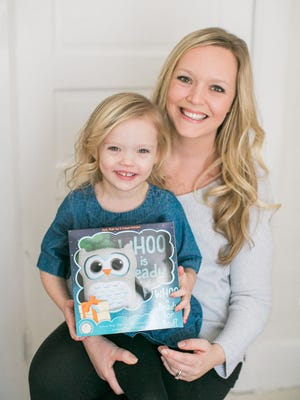 """Sitting in the lap of her mother Teryn Tilque, 3-year-old Addison holds the """"Whoo is Ready for Bed?"""" book package that includes a plush owl and a dry-erase crayon. Addison was Tilque's inspiration for writing and publishing the interactive children's book to help parents whose kids are prone to negative behaviors at bedtime."""