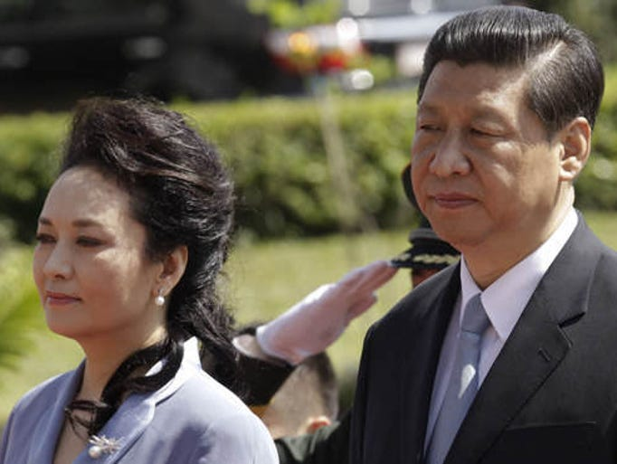 China's President Xi Jinping, right, and his wife Peng Liyuan listen to the national anthems of Costa Rica and China during their welcoming ceremony at the presidential house in San Jose, Costa Rica, Monday, June 3, 2013.  After Costa Rica, Xi has planned stops in Mexico and the United States. Trinidad, a leading supplier of natural gas, was their first stop of a four-country trip in the region.