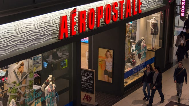 Shoppers passing by Aeropostale retail store inside a mall, the shop's window displays featuring mannequins wearing fashionable clothes.