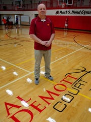 Al DeMott stands by the newly applied lettering on the basketball court that now carries his name.