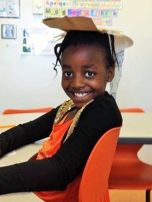 Edmunds second-grader Emeline Irishura, a student in Caitlin Mauren's class, shows off her protective hat invention, designed to protect the head and neck from the sun.