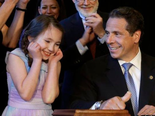 Gov. Andrew Cuomo, right, gets some help from Amanda Houser, 10, while signing a ceremonial bill to establish a medical marijuana program in New York on July 7, 2014.