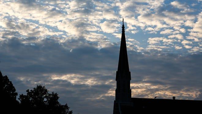 The sun rises over Sacred Heart Church on Marshall Avenue Tuesday morning.