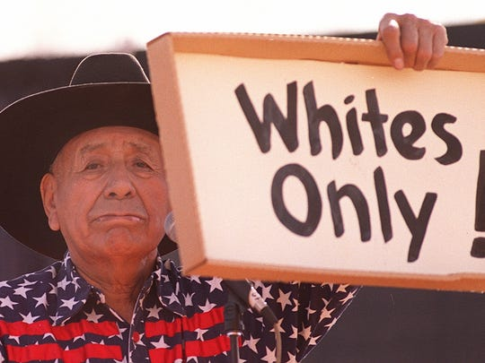 Native American Leon Grant, 76, holds up a sign which