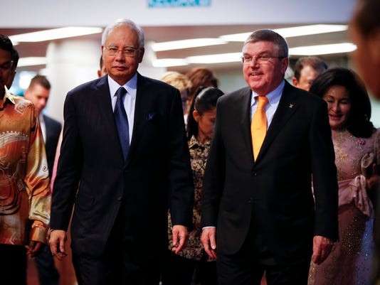 Malaysia's Prime Minister Najib Razak, center left, walks with President of the International Olympic Committee (IOC) Thomas Bach to the opening ceremony of IOC in Kuala Lumpur, Malaysia,Thursday, July, 30, 2015. Malaysia is hosting the 128th International Olympic Committee executive board meeting where the vote for the host cities of the 2022 Olympic Winter Games and for the 2020 Youth Olympic Winter Games will take place. (AP Photo/Vincent Thian)
