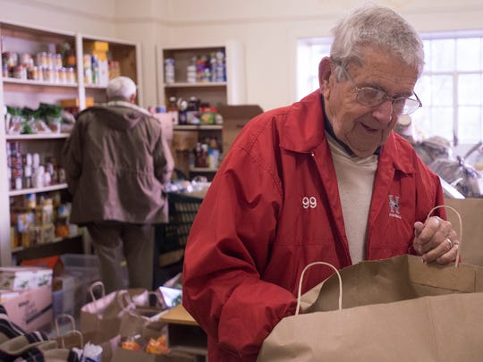 Charlie Lynn, a World War II veteran, looks through a bag of donated food while volunteering at the First Baptist Church Care Center in Montgomery on Wednesday.