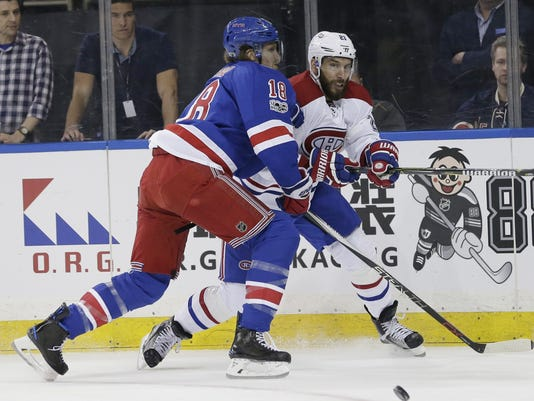 Montreal Canadiens' Dwight King, right, takes a shot past New York Rangers' Marc Staal during the first period in Game 3 of an NHL hockey first-round playoff series, Sunday, April 16, 2017, in New York. (AP Photo/Seth Wenig)