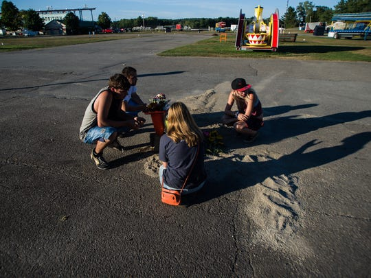 Friends of Ryan Durkin mourn Tuesday night at the place where he was fatally stabbed at the Champlain Valley Fair on Sunday night, Sept. 4, 2016.