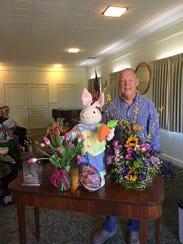 Tom Camp, of Lucile's Flowers, presents a floral arrangement