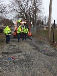 Crew repairing potholes in Milford on behalf of Domino's.