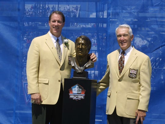 Jim Kelly, left, stands next to his bust with his presenter and former head coach Marv Levy after his induction into the Pro Football Hall of Fame on Aug. 3, 2002 at Fawcett Stadium in Canton, Ohio.