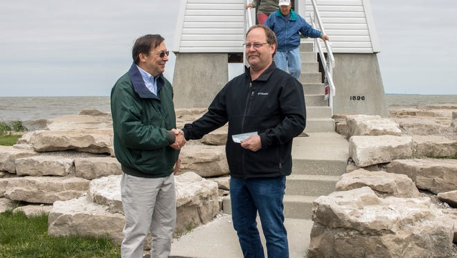 Richard Norgard, left, president of the Port Clinton Lighthouse Conservancy, last year presented the first $1 check for a year's rent to Port Clinton Mayor Hugh Wheeler.