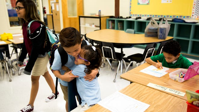 Khloe Lopez, 6, receives a hug from her brother Ethan Lopez, 9, and her sister Brionna Lopez, back left, 11, and the rest of her family, not pictured, as they wish her goodbye on her first day at Corkscrew Elementary on Wednesday, Aug. 16, 2017, in Golden Gate Estates.