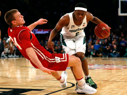 Wisconsin Badgers guard Brad Davison (34) commits a blocking foul against Michigan State Spartans guard Cassius Winston (5) during first half 2018 Big Ten Tournament quarterfinals at Madison Square Garden.